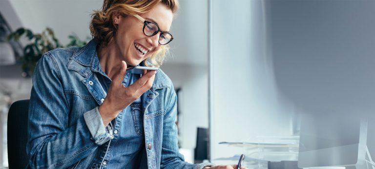 En smilende kvinne som snakker med en kunde på telefon