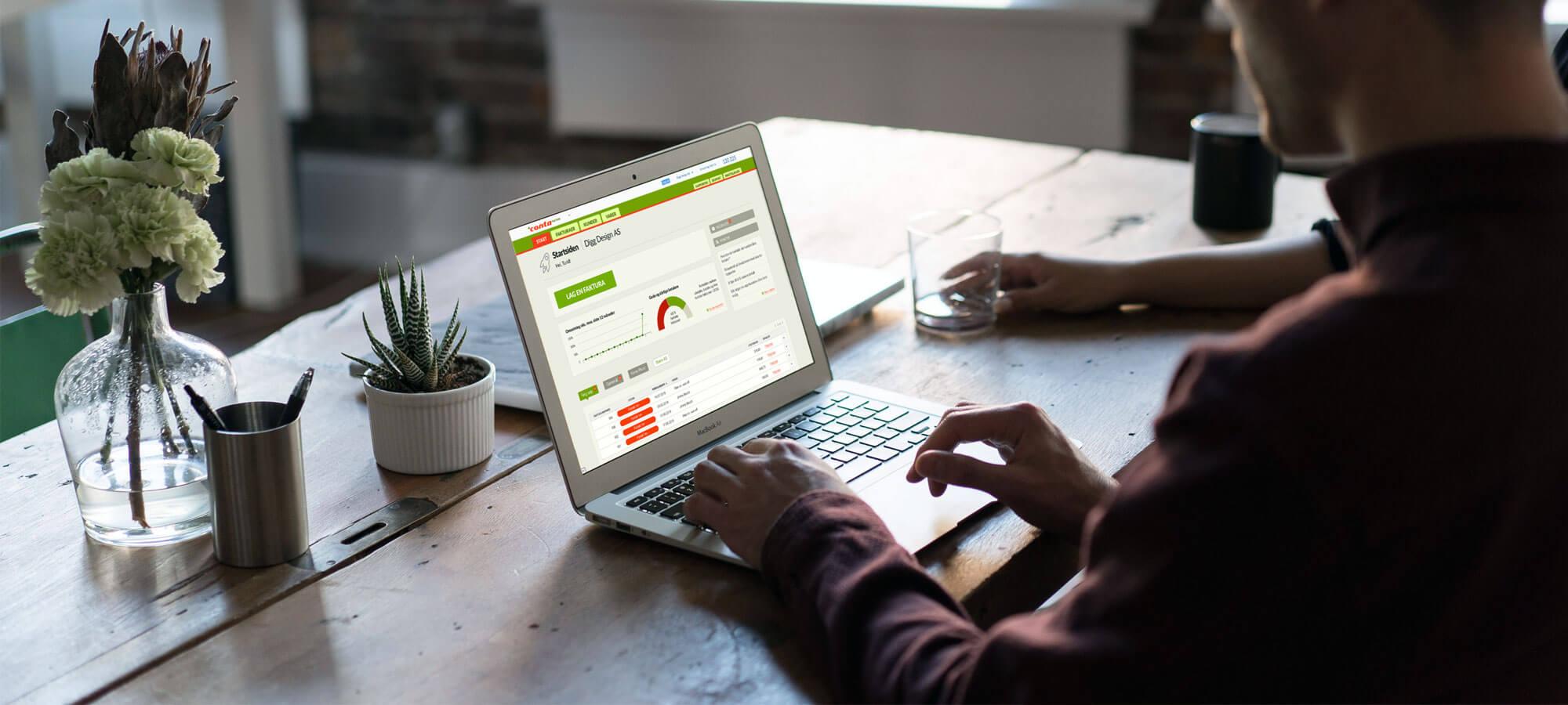 Mann som jobber med Conta Faktura på laptopen