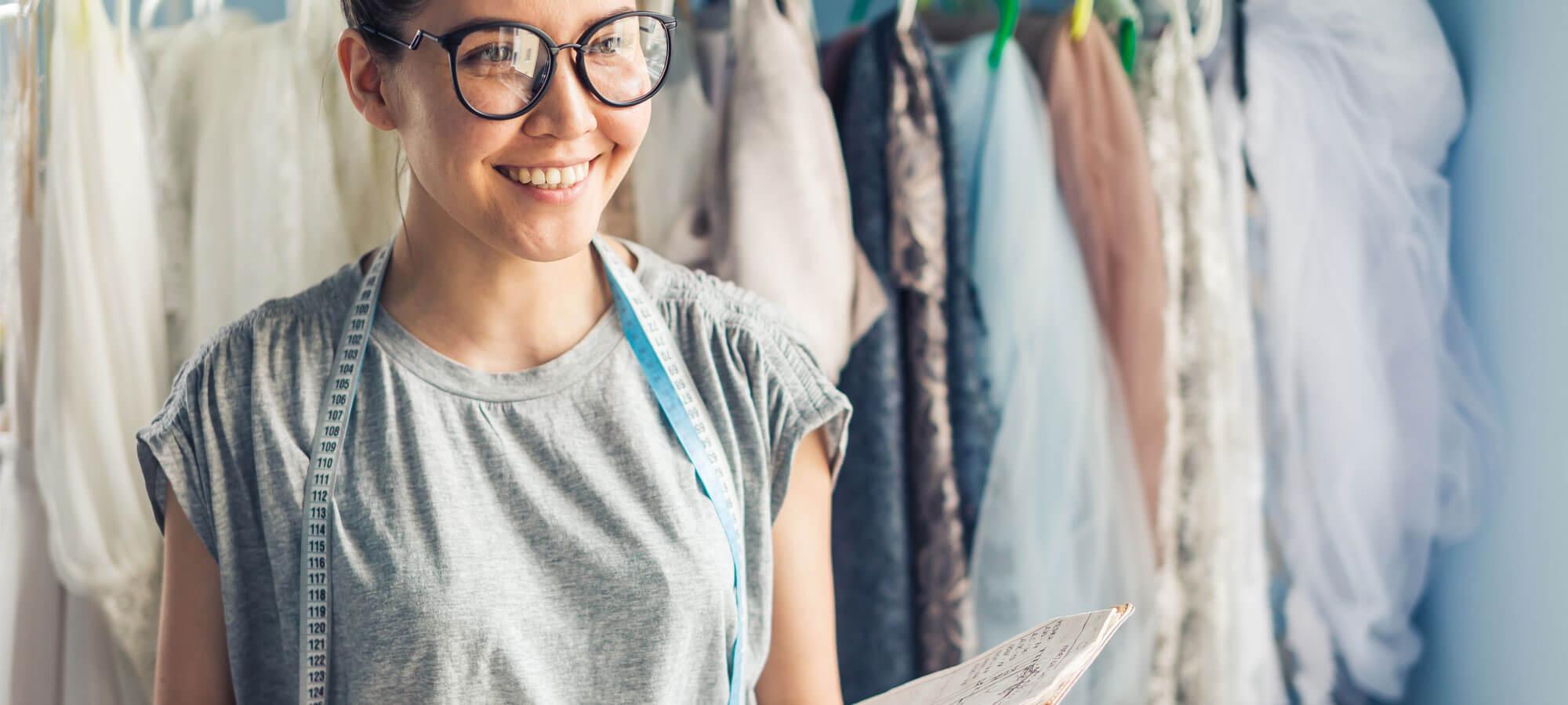 Klesdesigner som smiler med en notatbok i armene