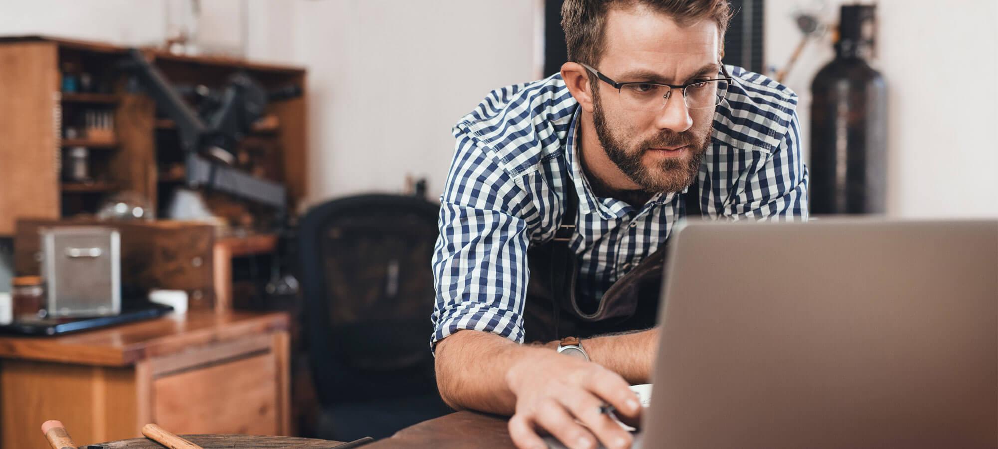 Mann med laptop på en arbeidsbenk