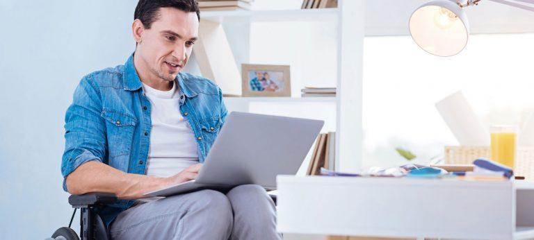 Mann i rullestol som arbeider på en laptop