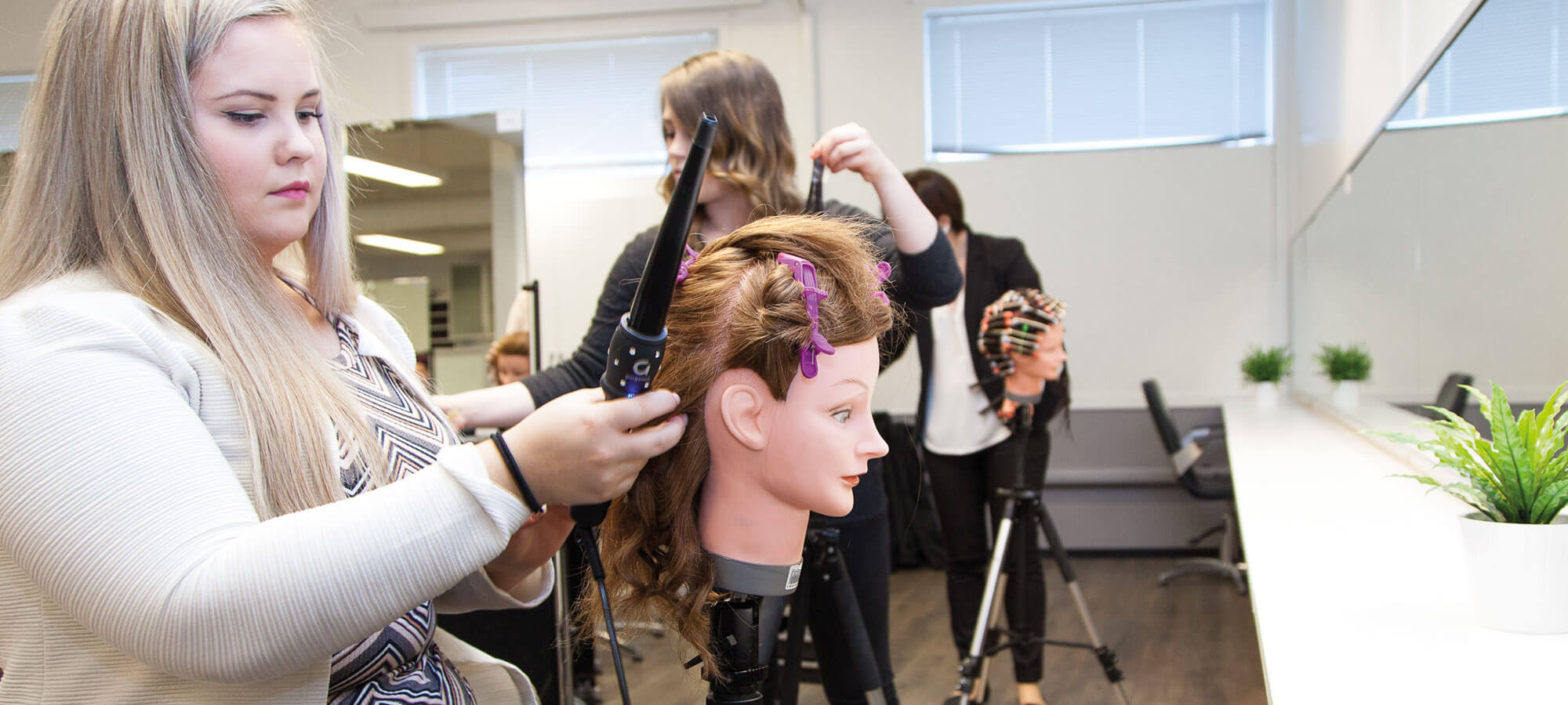 Elev som klipper en dukke