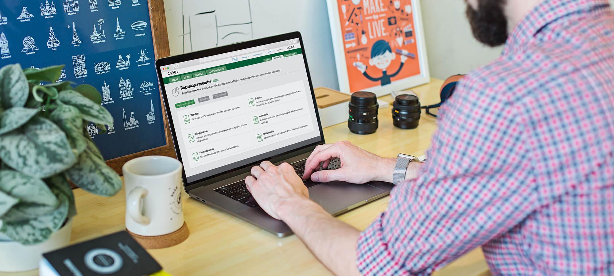 mann som sitter ved laptop og fører regnskap i conta.